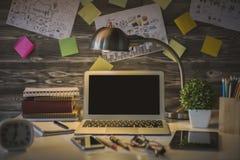 Posto di lavoro scuro con il computer portatile Immagini Stock Libere da Diritti