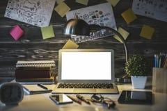 Posto di lavoro scuro con il computer portatile bianco Immagine Stock Libera da Diritti