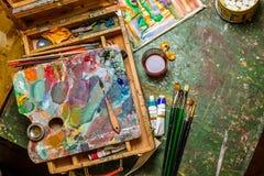 Posto di lavoro variopinto dell'artista con le spazzole e le pitture ad olio Fotografia Stock