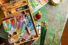 Posto di lavoro variopinto luminoso dell'artista con le spazzole e le pitture ad olio Fotografia Stock