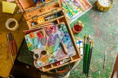 Posto di lavoro variopinto luminoso dell'artista con le spazzole e le pitture ad olio Immagini Stock