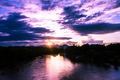 Posto di tramonto sopra la superficie del fiume ed il cielo come fondo Fotografia Stock