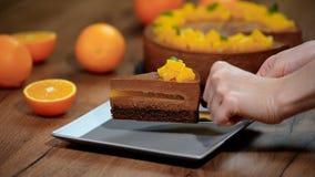 Posto em uma placa um a parte de bolo alaranjado da musse do chocolate filme
