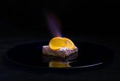 Postre anaranjado con el fuego Fotos de archivo