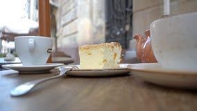 Postre caseoso con una taza de café y de una tetera de té en la tabla almacen de metraje de vídeo