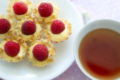Postre de la frambuesa con una taza de té Foto de archivo