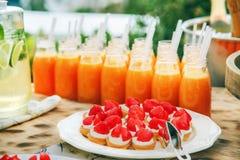 Postre de la fresa con crema en una placa blanca y una botella de j Foto de archivo libre de regalías