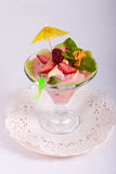 Postre de la fruta con la crema, menta, fruta fresca en bol de vidrio Imagenes de archivo
