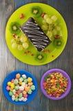 Postre de las uvas de la torta y de la fruta, kiwi, granada en un woode Imágenes de archivo libres de regalías