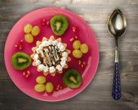 Postre de las uvas de la torta y de la fruta, kiwi, granada en un woode Imagen de archivo libre de regalías