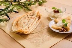 Postre del ` s del Año Nuevo Una rama de un árbol fue comida en una tabla Crepes del desayuno con crema agria, las nueces en una  Imagen de archivo libre de regalías