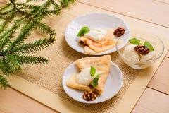 Postre del ` s del Año Nuevo Una rama de un árbol fue comida en una tabla Crepes del desayuno con crema agria, las nueces en una  Fotos de archivo