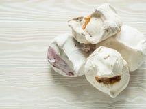 Postre dulce - merengue con diverso relleno en el fondo de madera blanco foto de archivo