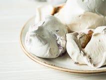 Postre dulce - merengue con diverso relleno en una placa imagen de archivo