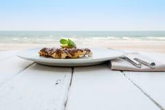 Postre en la playa, opinión del chocolate dulce del mar Imagenes de archivo