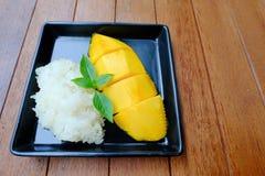 Postre famoso tailandés: Mango con el desmoche del arroz pegajoso con leche de coco Foto de archivo