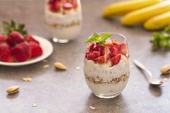 Postre helado hecho en casa del yogur con el granola, las fresas, los pl?tanos y las semillas de Chia en vidrios Postre de la die fotografía de archivo