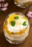 Postre helado hecho estallar de la quinoa, del yogur y del melocotón imagenes de archivo