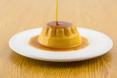 Postre o cospel de las natillas de la vainilla del caramelo de nata en el plato blanco Imagen de archivo libre de regalías