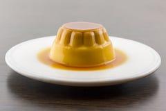 Postre o cospel de las natillas de la vainilla del caramelo de nata en el plato blanco Fotos de archivo