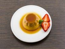 Postre o cospel de las natillas de la vainilla del caramelo de nata en el plato blanco Foto de archivo
