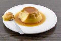 Postre o cospel de las natillas de la vainilla del caramelo de nata en el plato blanco Imagen de archivo