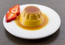 Postre o cospel de las natillas de la vainilla del caramelo de nata en el plato blanco con Imagen de archivo