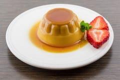 Postre o cospel de las natillas de la vainilla del caramelo de nata en el plato blanco con Foto de archivo