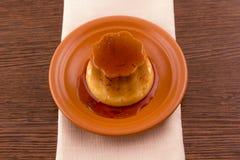 Postre o cospel de las natillas de la vainilla del caramelo de nata en plato Foto de archivo