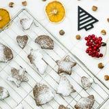 Postre picante del invierno de la Navidad - galletas del jengibre asperjadas con el azúcar en polvo Imagenes de archivo