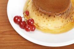 Postre poner crema del caramelo con las pasas rojas Fotografía de archivo