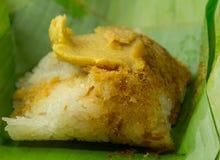 Postre tailandés, arroz pegajoso con las natillas cocidas al vapor, envueltas en banan Fotografía de archivo