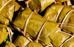 Postre tailandés, plátano con el arroz pegajoso cubierto en el khao tom de la hoja del plátano enojado Fotos de archivo