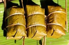 Postre tailandés, plátano con el arroz pegajoso cubierto en el khao tom de la hoja del plátano enojado Imagenes de archivo