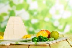 Postre tradicional del queso de Pascua, huevos coloreados, flores en fabr fotografía de archivo