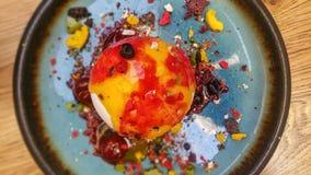 Postre - una bola del helado de vainilla con el jarabe desde arriba en una placa de cerámica Imágenes de archivo libres de regalías