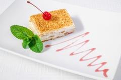 Postre Una torta deliciosa o un pedazo de torta, con un top de la cereza, y hojas de menta, en una placa blanca Marco horizontal Fotos de archivo