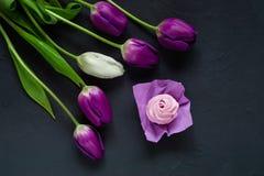 Postre y ramo de tulipanes púrpuras en un fondo oscuro, espacio para el texto foto de archivo libre de regalías