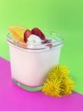 Postre: yogur con las fresas, las pasas, la crema y la naranja Foto de archivo