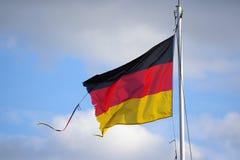 Postrzępiona flaga trzepocze w wiatrze przeciw niebieskiemu niebu Niemcy Obraz Stock