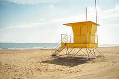 Posts amarillos del salvavidas en una playa vacía fotos de archivo