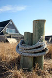 Posts on Beach. Large posts and thick rope, place to tie boat, house in background, sea grasses and sunshine Stock Images