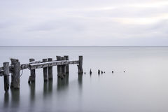 Posts of a broken pier leading out into calm blue tranquil sea w Stock Photo