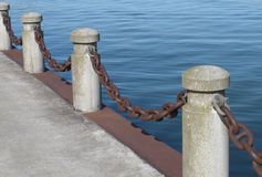 Posts and chain on a pier. Row of concrete posts linked by a heavy rusty chain along the edge of a pier, with blue water in the background Royalty Free Stock Images