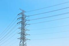 posts de alto voltaje de la electricidad con los cables y el cielo azul Foto de archivo