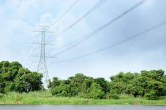 Posts de alto voltaje de la electricidad debajo del cielo nublado Fotos de archivo