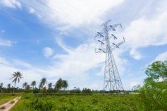 Posts de alto voltaje en campo verde Fotos de archivo