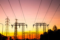 Posts de alto voltaje en el tiempo crepuscular Foto de archivo libre de regalías