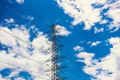 Posts de la electricidad en las nubes del cielo azul Imagen de archivo libre de regalías