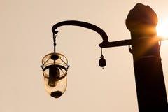 Posts de la lámpara de calle del diseño en escena determinada del sol Imágenes de archivo libres de regalías